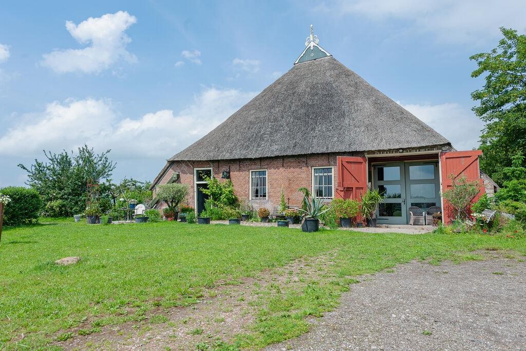Karakteristieke kop-hals-rompboerderij met roeibootje, waterrijke Lauwersgebied - Boerderijvakanties.nl