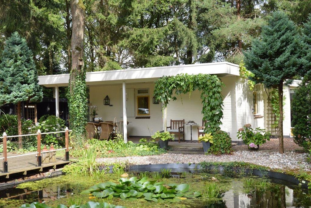 Vrijstaande bungalow met buitenhaard, overdekt terras en vijver op bosperceel - Boerderijvakanties.nl