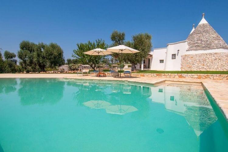 Een typische trullo in het platteland met infinity zwembad en terras met BBQ