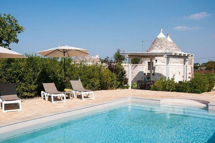 Typisch Pugliese Trullo met gedeeld zwembad midden in een wijngaard